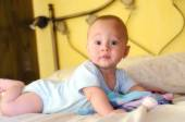 Baby built on the bed looking curiously — Zdjęcie stockowe