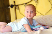 Baby built on the bed looking curiously — Stock Photo