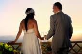 Groom and bride toasting on a terrace eye contact rear view — Stock Photo