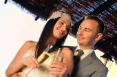 Groom and bride toasting on a terrace smiling eye contact — Stock Photo