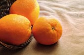 Oranges out of a basket on a table with  brown tablecloth closeu — Stock Photo