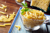 Uncooked macaroni composition in a glass bowl — Stock Photo