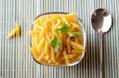 Uncooked macaroni in a bowl on a bamboo tablecloth top view — Stock Photo