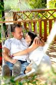 Young couple on a rope hammock in a cottage rear view — Stock Photo
