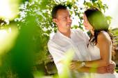 Young couple looking accomplices among trees — Stock Photo