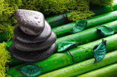 Stack of black stones for massage on bamboo top view — Stock Photo