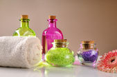 Oils and bath salts on white glass table — Stock Photo