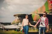 Fun and stylish couple walking near the aircraft — Stock Photo