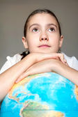 Dreaming about the future. Pretty girl with blue globe. — Stock Photo