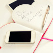 Smartphone and Valentine love message in heart shape notebook. — Stock Photo #64458981