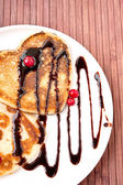 Heart shaped pancakes with chocolate sauce and cranberries. — Stock Photo