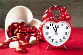 Valentine love heart shaped red love clock with sweet chocolates — Stock Photo
