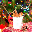 Cup with cinnamon sticks on festive christmas tree background. — Stock Photo #64538371