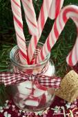 Bunch of red and white striped candy canes in glass jar on chris — Stock Photo