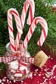 Many striped candy canes in glass jar on christmas background — Stock Photo