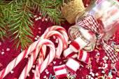 Sweet candies spilled from glass jar. Green fir christmas — Stock Photo