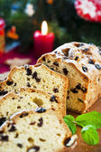 Sliced fruitcake with raisins and mint leaf on christmas backgro — Stock Photo
