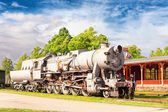 Old rustic steam locomotive on station platform. Cloudy sky back — Stock Photo