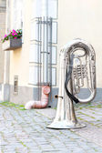 Big shiny base trumpet standing upturned on old town street. — Stock Photo