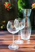 Two transparent shiny empty wineglasses and carafe in rays of su — Stock Photo