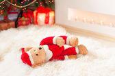 Santa tedyy bear toy lie on sheepskin near illuminated christmas — Stock Photo