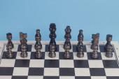 Wooden dark brown chess set blue background. — Stock Photo