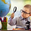 Boy looking through magnifying glass at globe — Stock Photo #52918687