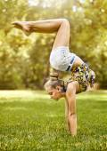 Jong meisje doen stretching oefening op groen gras in park — Stockfoto