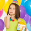 Little girl with gift box and colorful balloons on birthday party — Stock Photo #58224803