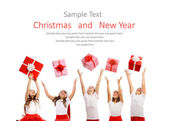 Group of happy kids in Christmas hat catching gift boxes — Stock Photo