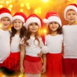 Happy kids in Christmas hat with colorful lights on background — Zdjęcie stockowe #58825079