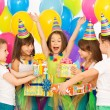 Joyful little kid girl receiving gifts at birthday party — Stock Photo #58869077