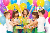 Joyful little kid girl receiving gifts at birthday party — Stock Photo