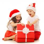Happy kids in Santa hat opening a gift box — Stock Photo