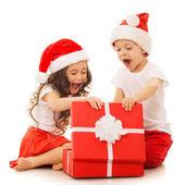 Happy kids in Santa hat opening a gift box — Foto de Stock