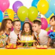 Kids celebrating birthday party and blowing candles on cake — Stock Photo #62105385