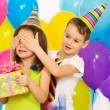 Joyful little kid girl receiving gifts at birthday party — Stock Photo #62105671