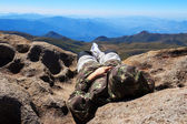 Man laying on edge of mountain peak — Stock Photo