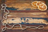 Background wooden table with christmas chaplet and pieces of dri — Stock Photo
