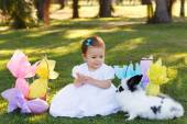 Smiling baby girl looking at rabbit with Easter chocolate eggs — Stock Photo