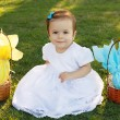 Cute smiling baby girl on green grass with Easter chocolate eggs — Stock Photo #69103681