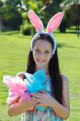 Smiling happy teen girl with rabbit ears and Easter chocolate eg — Stock Photo