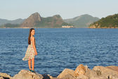 Beautiful young teen girl smiling, standing on stones near sea i — Stock Photo