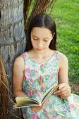 Cute teen girl reading book sitting on green grass — Stock Photo
