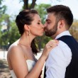 European bride and groom kissing in the park — Stock Photo