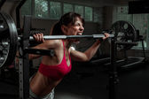 Beautiful sports fitness girl with a barbell — Stockfoto