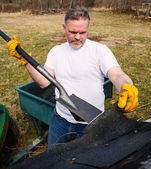 Man taking shingles off a shed roof — Stock Photo