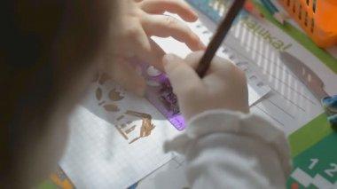 Child draws using a stencil. — Stock Video