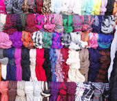 Colorful hanging scarves in shop — Stock Photo
