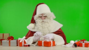 Santa Claus is Wrapping a Gift with Red Colored Paper — Stock Video
